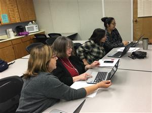 Four school secretaries look at laptops during a training